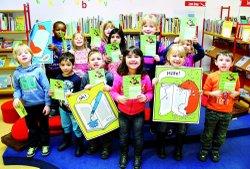 Stolz zeigen die Kinder ihren Bibliotheksführerschein in die Kamera.